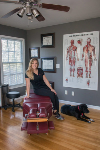 Dr. Meghan Faulkner posing on chiropractic bench