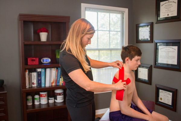 Dr. Meghan Faulkner applying kinesiology taping to young man
