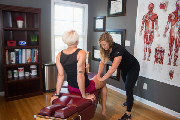 Dr. Meghan Faulkner evaluating blond woman's knee