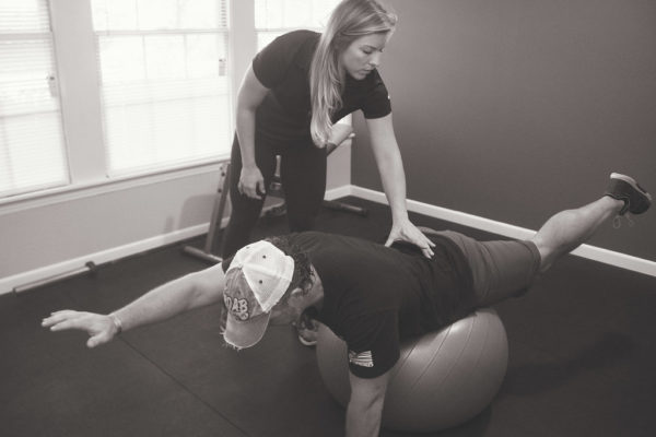 Dr. Meghan Faulkner helping man balance on stomach on workout ball black and white photo