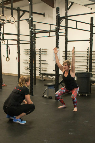 Dr. Meghan Faulkner assessing woman's movements in a gym