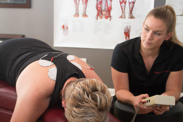 Dr. Meghan Faulkner watching female patient do electrical muscle stimulation