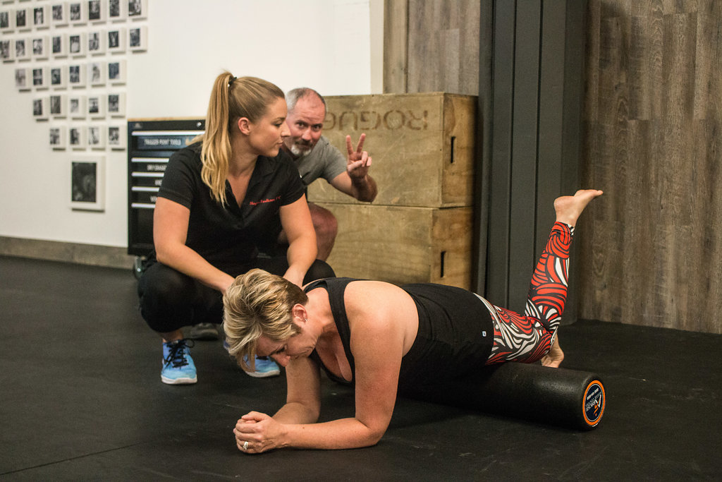 Dr. Meghan Faulkner evaluating blond woman using foam roller